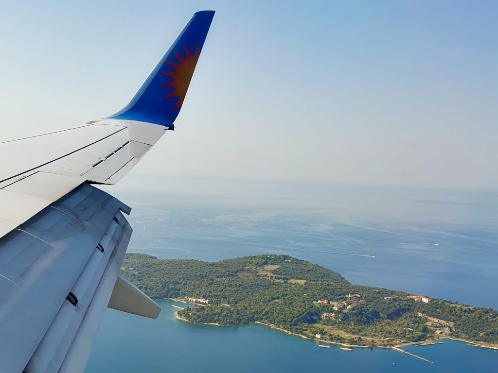 Taken from the window seat of a Jet2 plane on the approach to Pula from the west. You can see a white wing, with the flaps deployed with a blue tip containing half a sun (cut vertically down the middle). On the ground you can see a peninsula of Pula, with lots of forest and surrounded by the blue sea that goes into the horizon