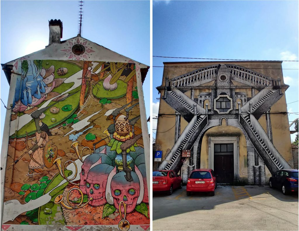 Two sides of buildings are shown both with whole-wall art murals. On the left is a more abstract artwork showing pink and blue skulls playing bugles as a single warrior walks along a path with a bow and arrow. On the right, two black and white staircases have been painted onto the side of the building, slightly obscured by the cars parked outside.