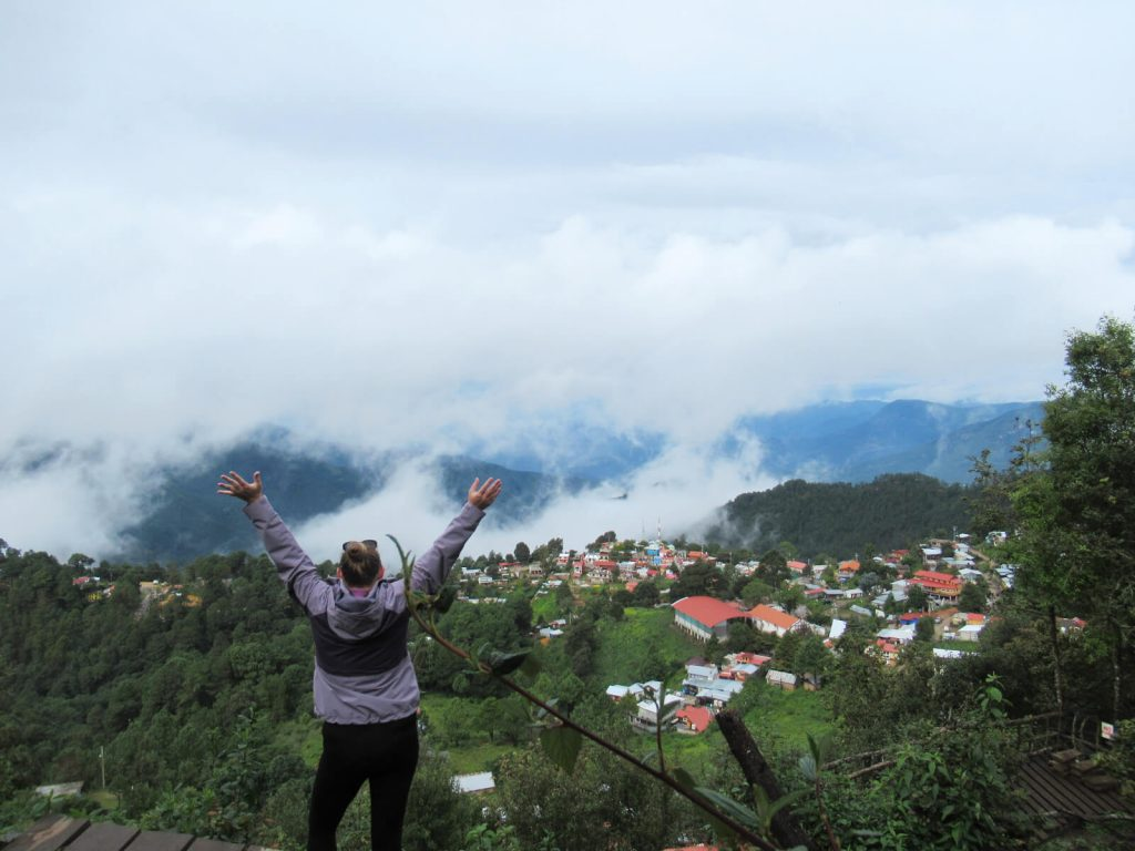 There are many things to do in San Jose del Pacifico including climbing to this mirador for impressive views. Zoe is stood looking away from the camera with both arms above her head. The clouds cover the mountains in the distance