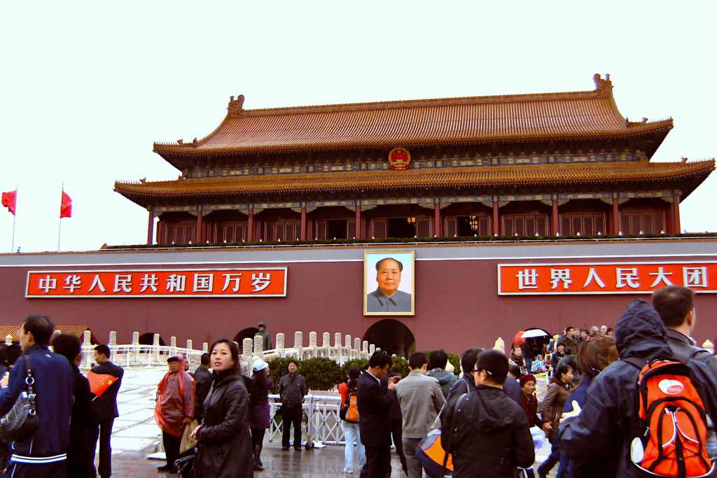 Forbidden City in Beijing, a pagoda style building with an image of Chairman Mao on the front, busy with tourists looking