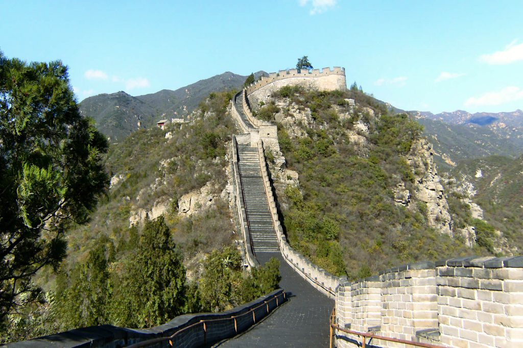 An uphill stretch of the Great Wall of China, visitable from Beijing on a daytrip. Either side is lush green trees and grass