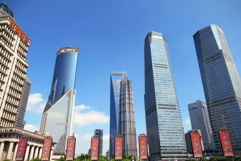 The Shanghai skyline from in front of the Pearl Oriental Tower during a layover with a China Transit Visa, the architecture varies greatly behind the buildings that rise into the crisp blue sky. Visit this during a layover with a China Transit Visa